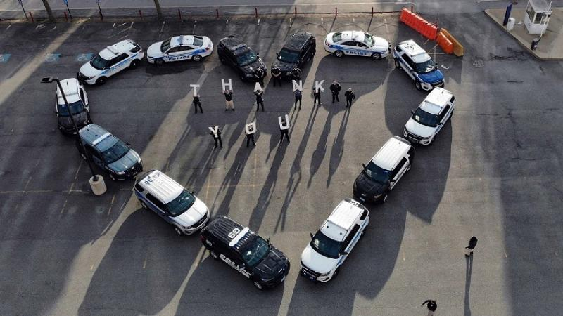 Cars are organized in the shape of a heart with people holding signs that read 'Thank You'.