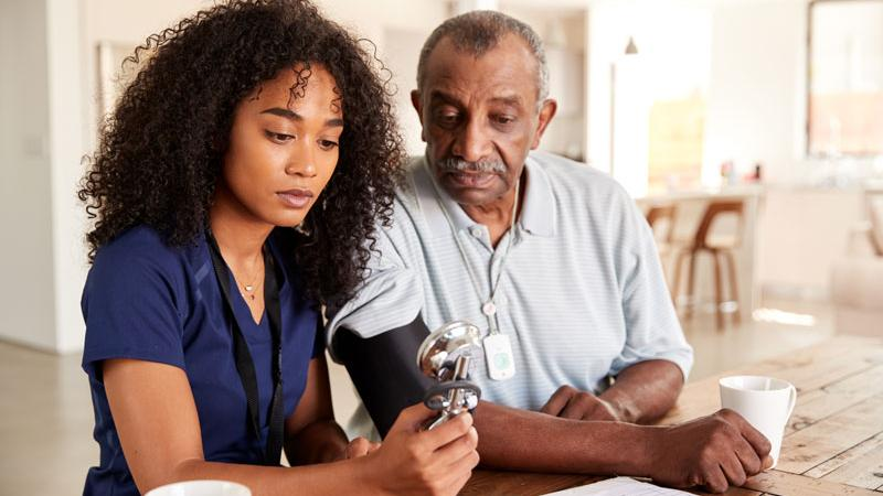 Doctor takes patient's blood pressure in patient's home.