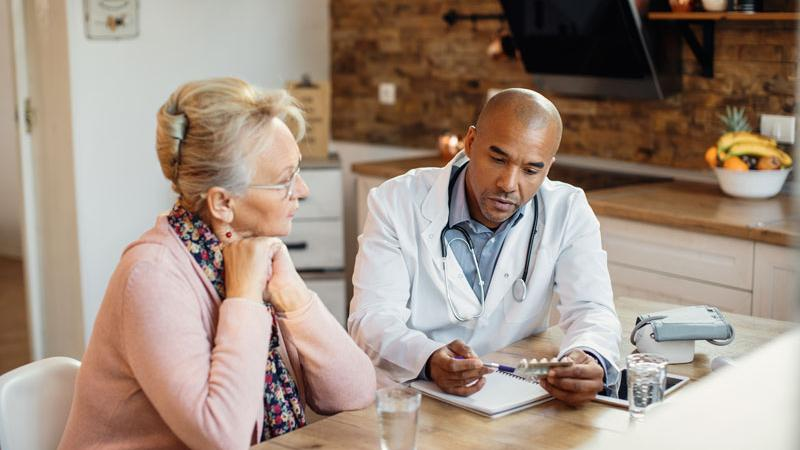 Doctor discusses treatment with patient in her home.